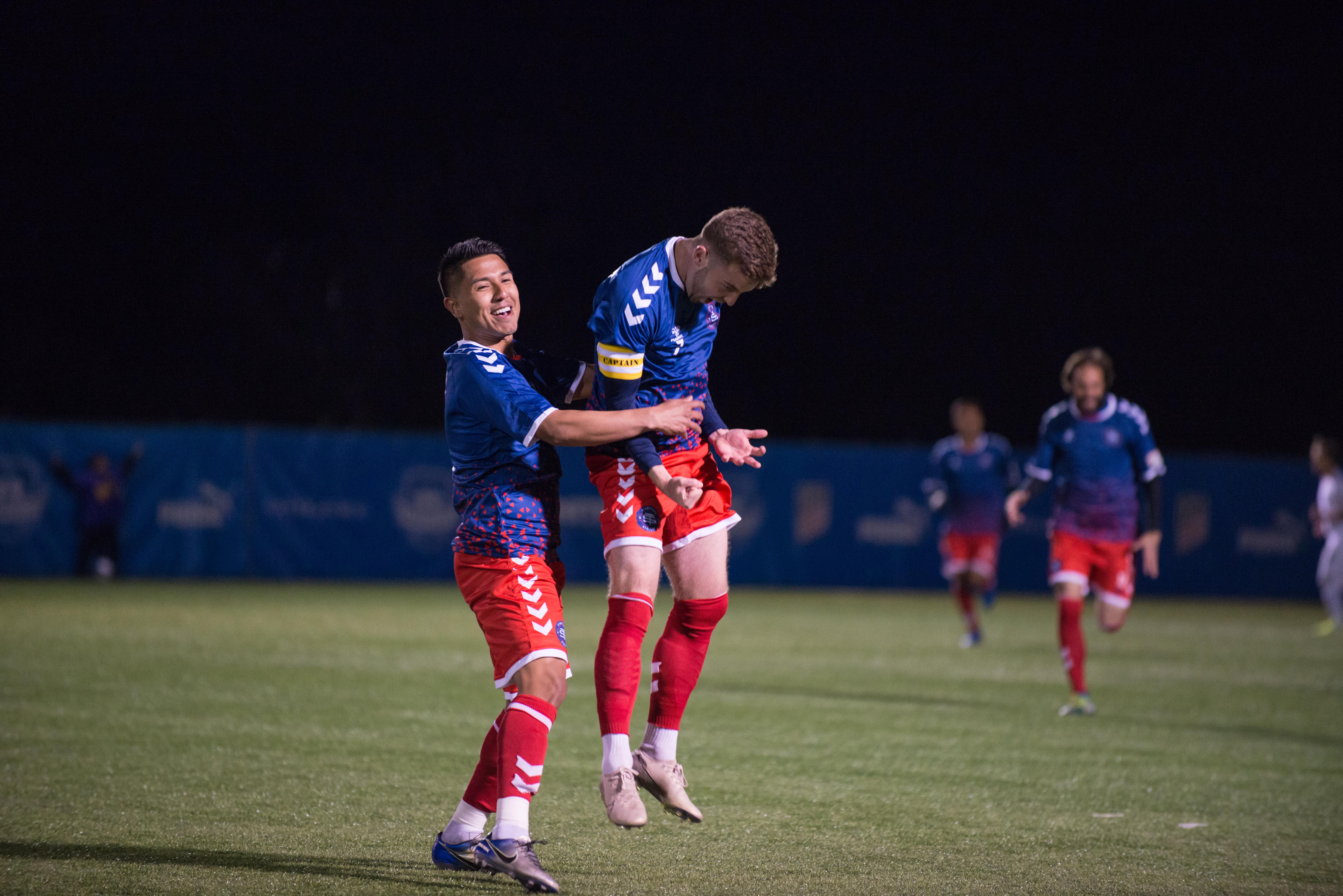Tate Robertson (right) celebrates a goal with Randy Mendoza (left)